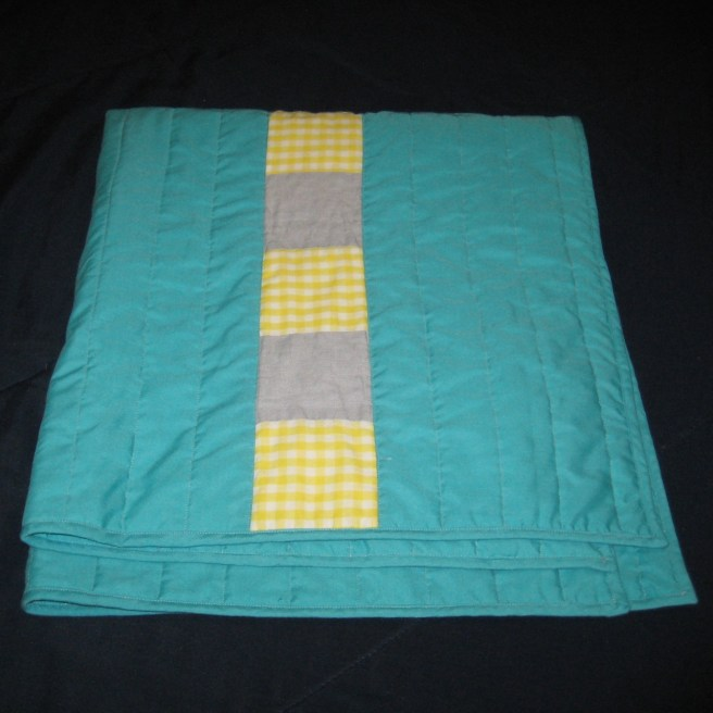 Photograph of folded aqua, yellow, and gray baby quilt