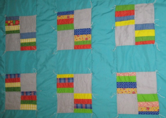 Photograph of aqua, gray, bed, yellow, red, and green baby quilt constructed from four-patch squares