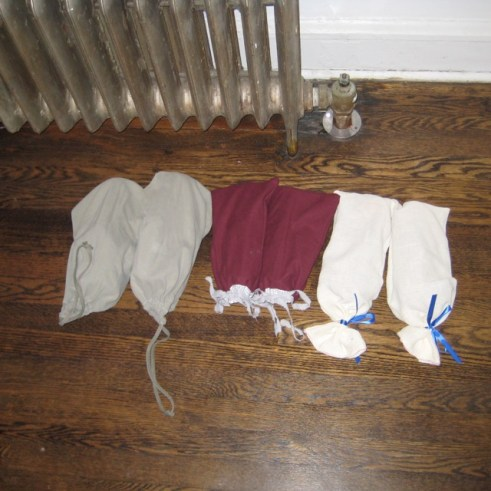 Photograph of three pairs of shoes in shoe bags on the floor next to a radiator