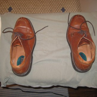 Photograph of brown dress shoes on top of sage green knit shirt