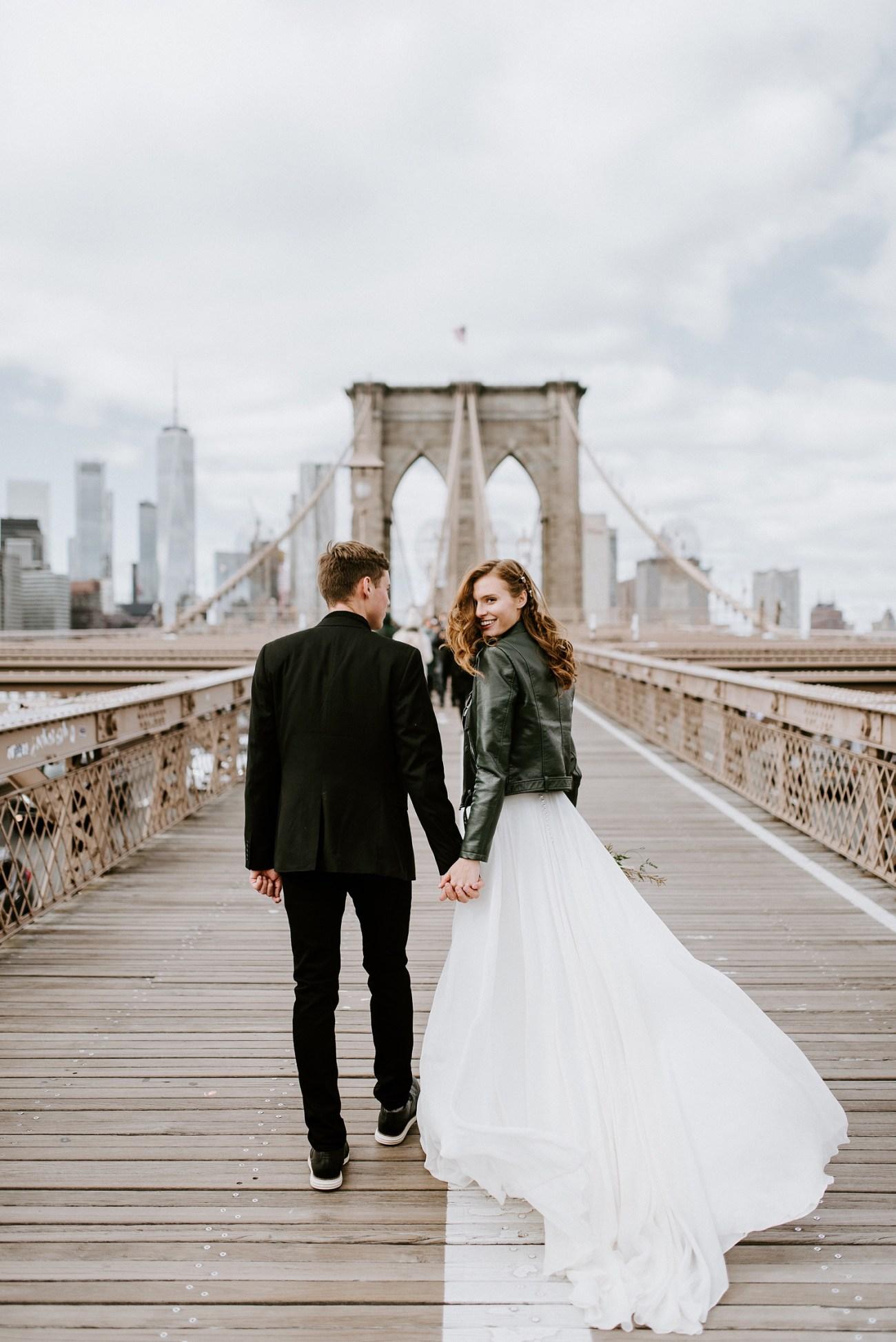 Bride and Groom walking on the Brooklyn Bridge for their bridal portrait. Brooklyn wedding photos. Dumbo Brooklyn Bride and Groom elopement photos. Anais Possamai Photography. New York Wedding Photographer