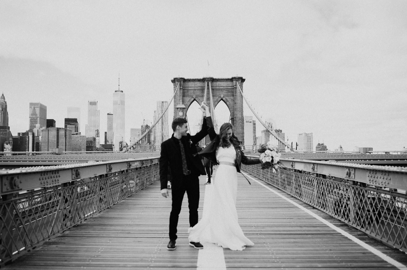 Bride and Groom dancing on the Brooklyn Bridge for their bridal portrait. Brooklyn wedding photos. Dumbo Brooklyn Bride and Groom elopement photos. Anais Possamai Photography. New York Wedding Photographer