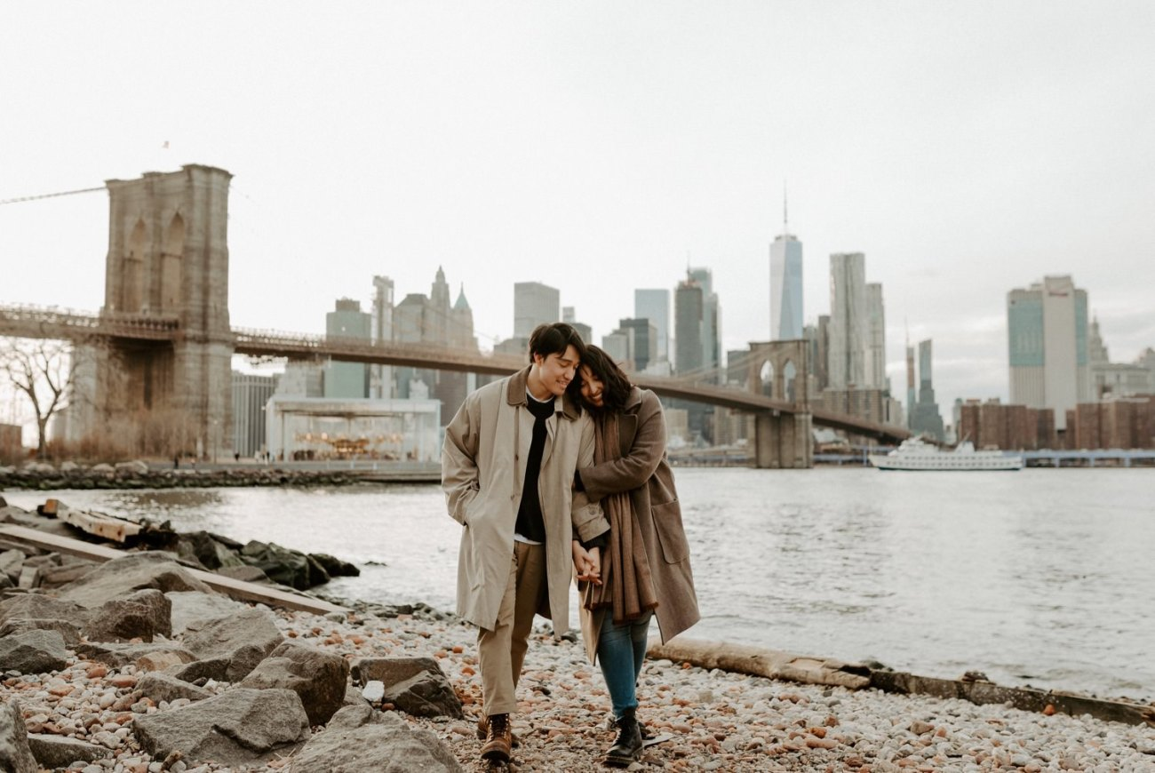 The best skyline views in Brooklyn Dumbo, Couple walking on Pebble Beach in Dumbo, Brooklyn