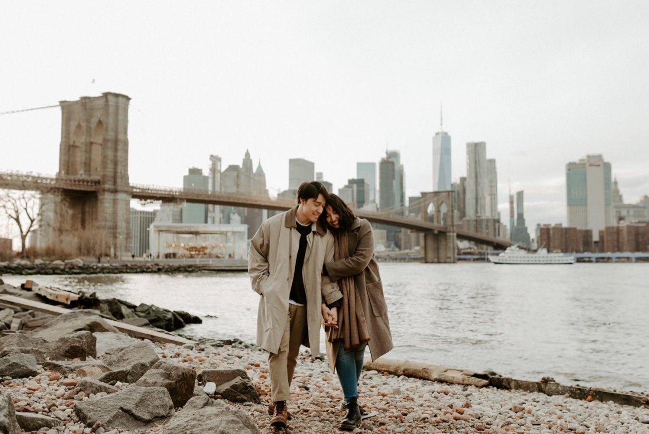 The best skyline views in Brooklyn Dumbo, Couple walking on Pebble Beach in Dumbo, Brooklyn
