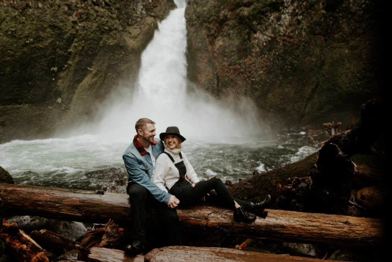 Couple seating on logs in front of Wahclella Falls in Oregon