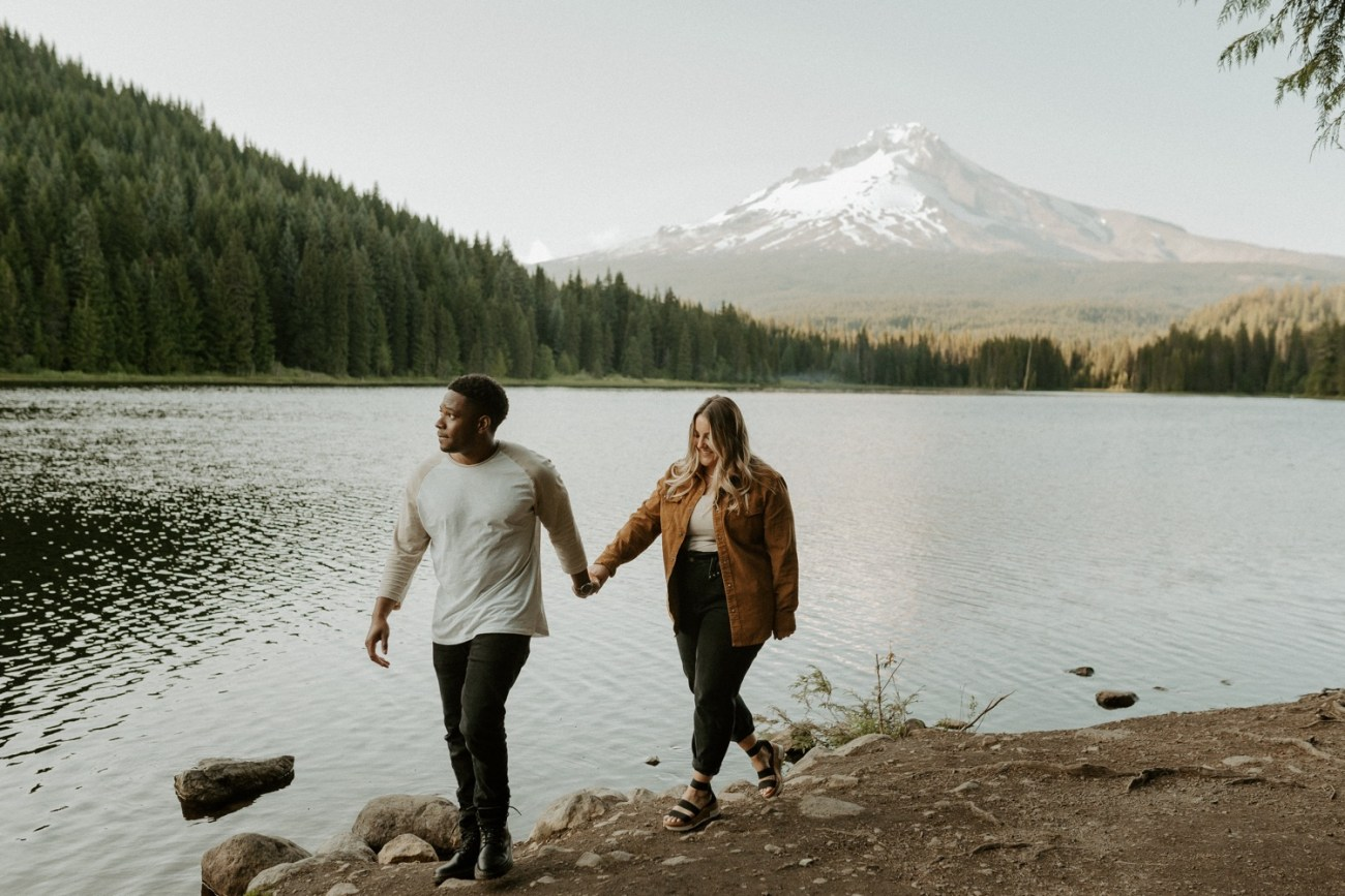 Couple walking by Trillium Lake and mount Hood, Early summer sunset engagement session in Mt Hood, Oregon