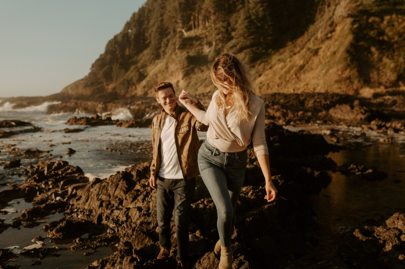 Couple walking on the lava rock in Yachats Oregon for their engagement photos. Anais Possamai Photography