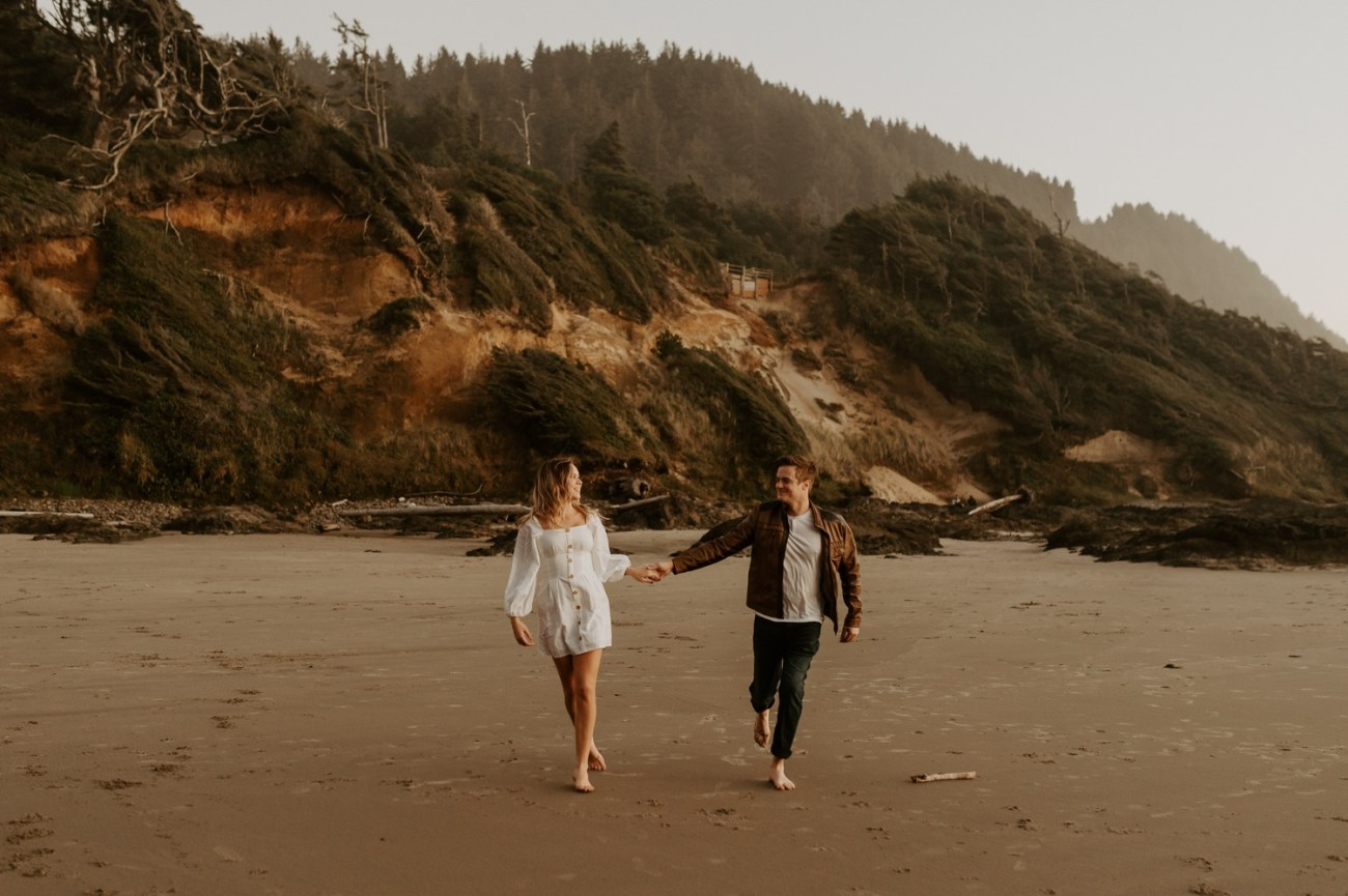 Couple running on the beach in Yachats for their engagement session. Anais Possamai Photography