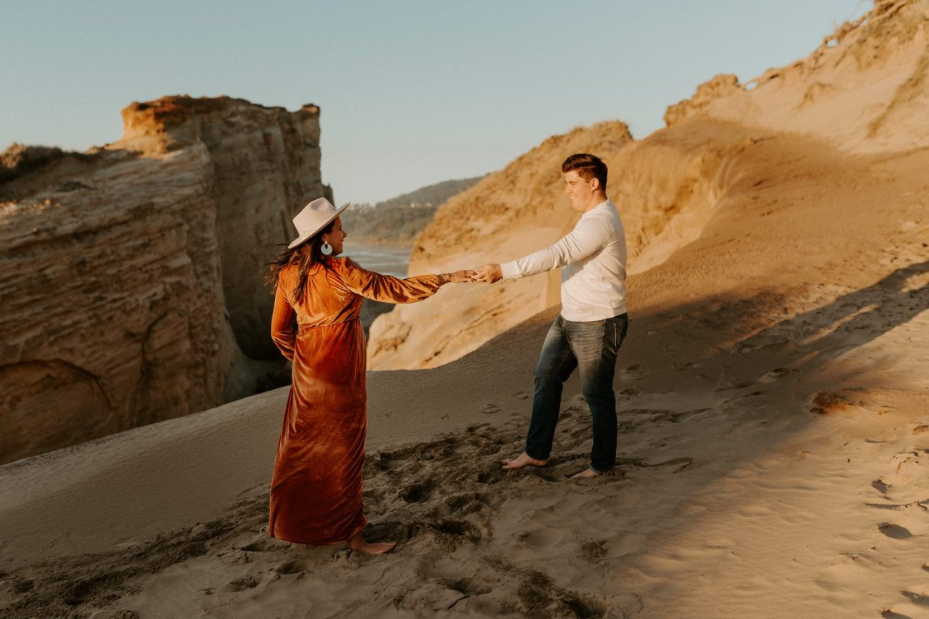 Couple dancing on the dunes of Cape Kiwanda for their maternity Session