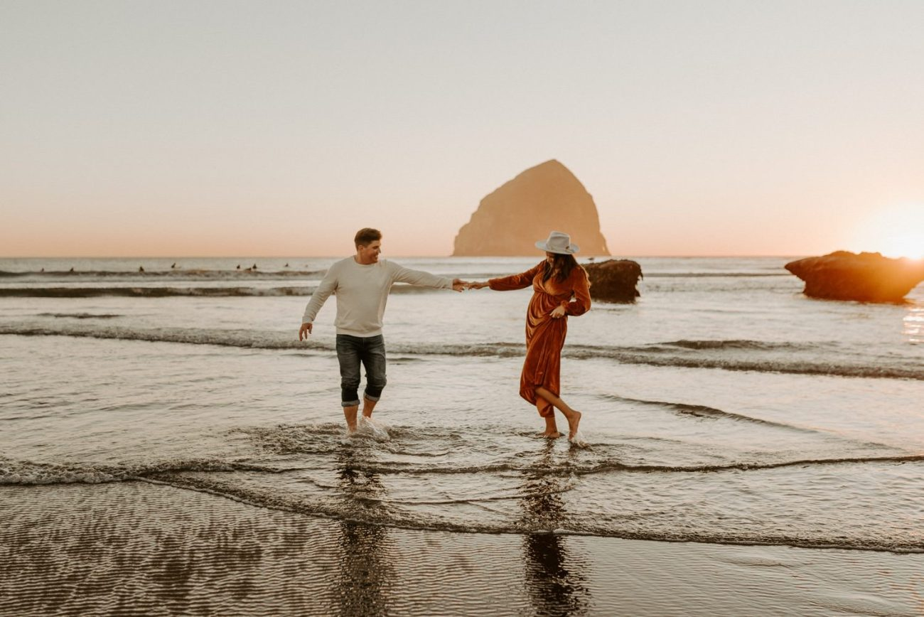 Couple walking in the waves of Cape Kiwanda Beach in Pacific City Oregon
