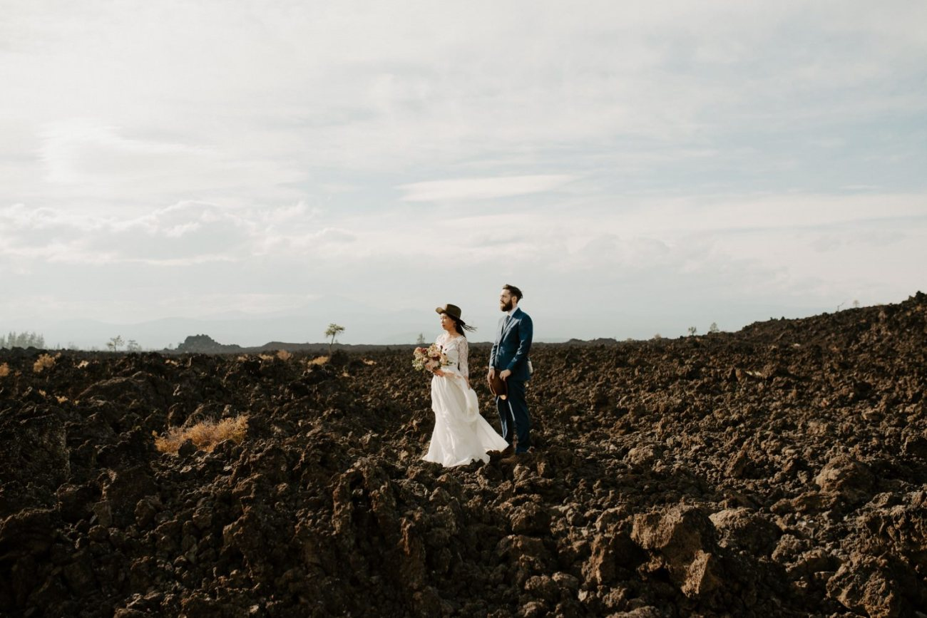 Bride and Groom standing on the lava rock in Newberry Volcano in Bend Oregon