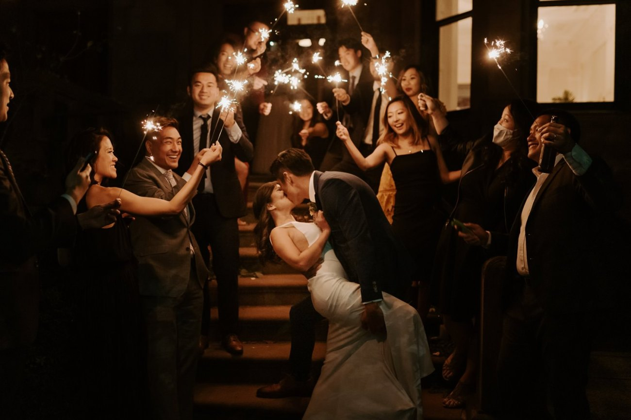Bride and Groom Sparkler exit on top of Brownstone House stairs in Brooklyn for their backyard wedding. Anais Possamai Photography
