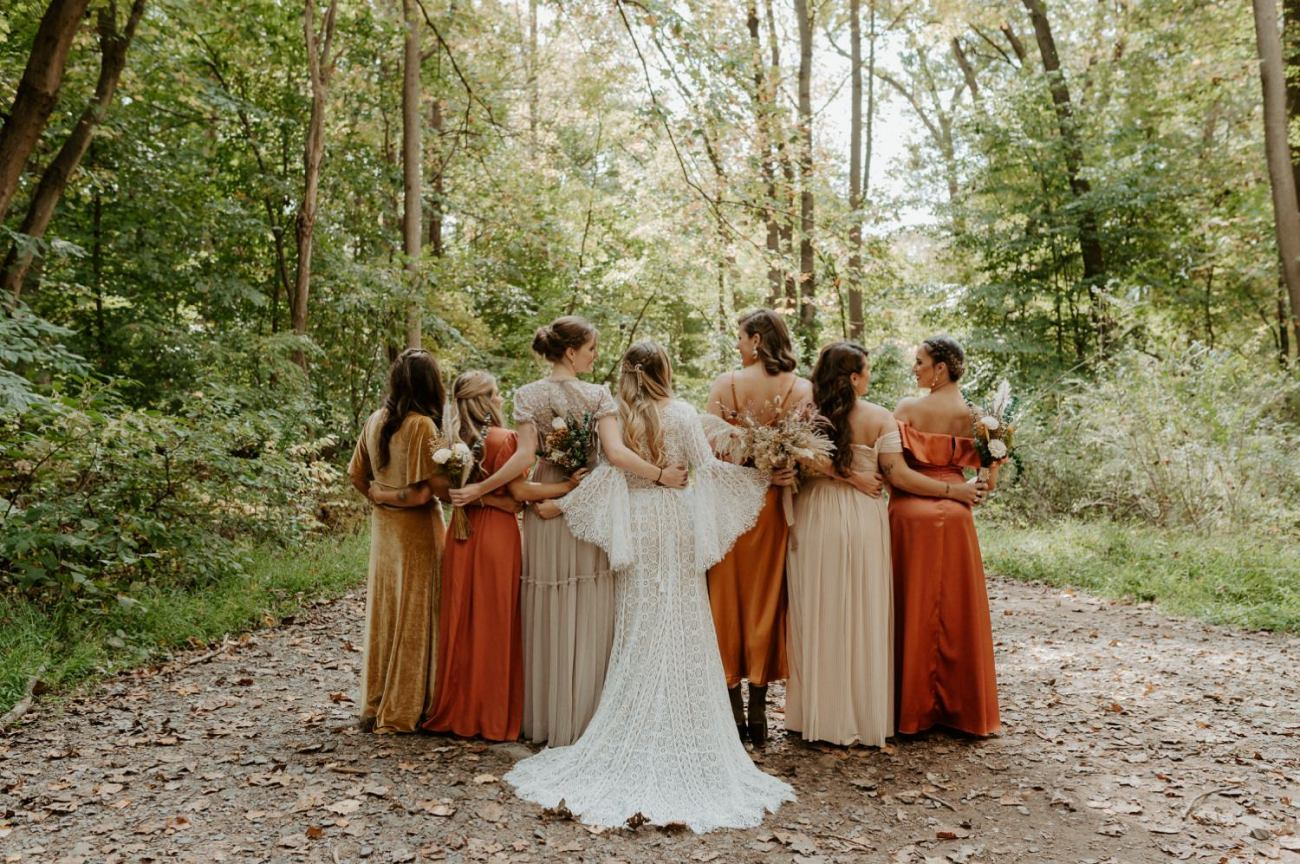 Bride and bridesmaid mismatched dresses with a neutral and orange color palette