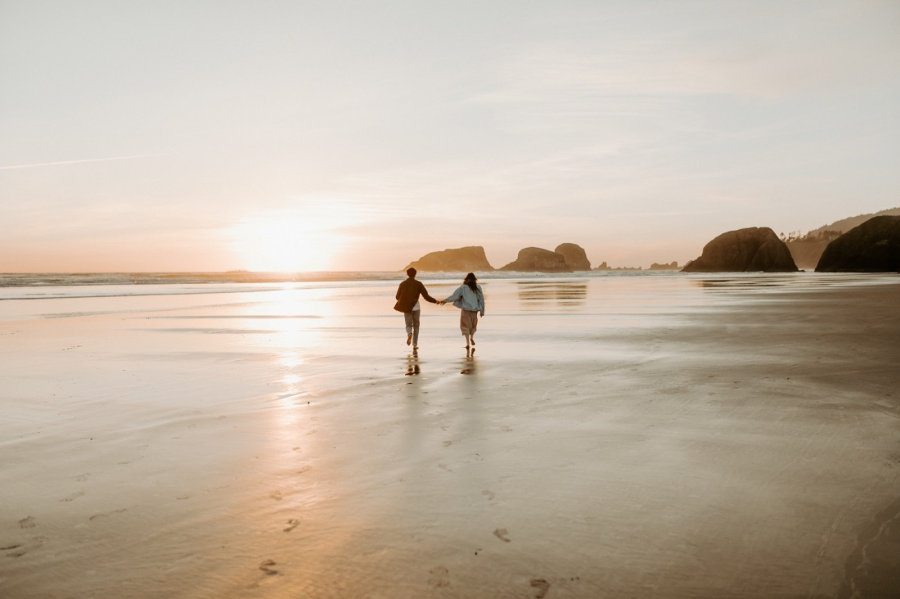 Couple running on Cannon Beach at sunset for their engagement session