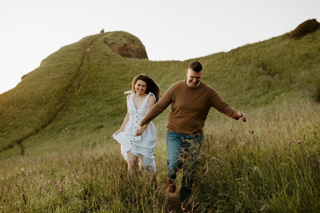 Couple running on God's Thumb trail for their engagement session