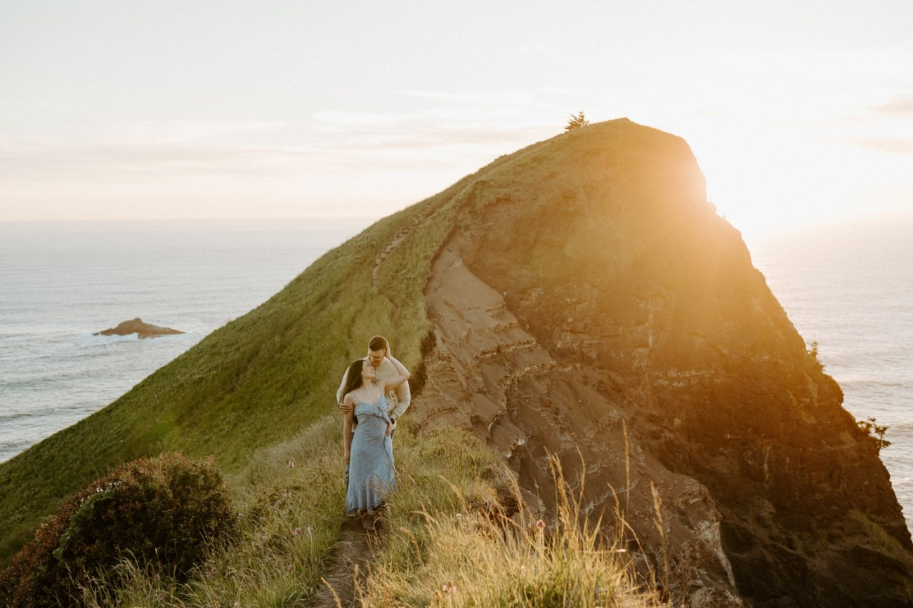 Couple standing on the edge of God's Thumb during sunset for their engagement session