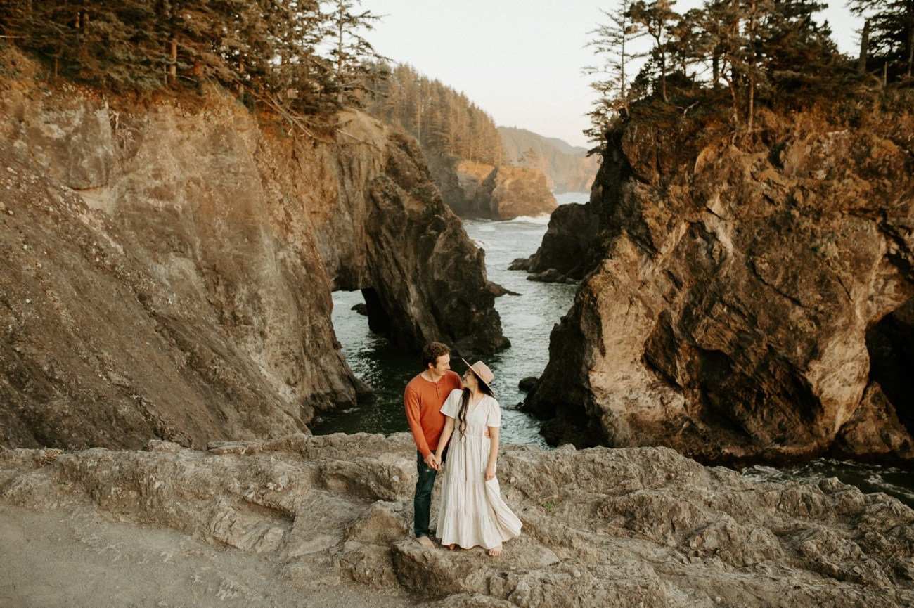 Couple standing in front of Natural Bridges in Samuel H Boardman for their engagement session