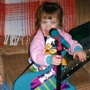 Ana Playing with Toy Guitars and Microphones at an Early Age.