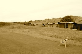 A row of beach huts sit tucked in between the 16th hole and the adjacent foredune.