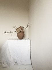 pale blush interiors with an antique amphorae and dried hydrangea