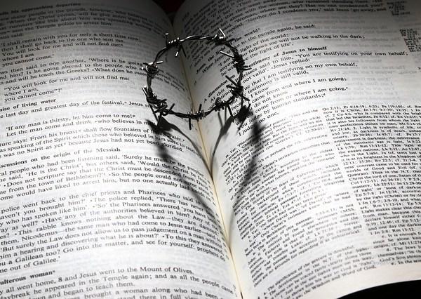 L'Amour de Dieu représenté par une Bible et l'ombre d'une couronne d'épine formant un cœur.
