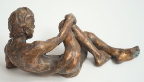 lateral view of bronze sculpture of a male nude leaning on his ellbow