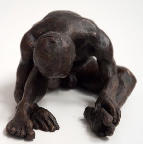 frontal view of a bronze sculpture of a male nude sitting with his head on his knee