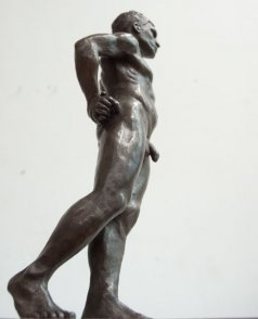 caudal lateral view of bronze sculpture of standing male nude figure