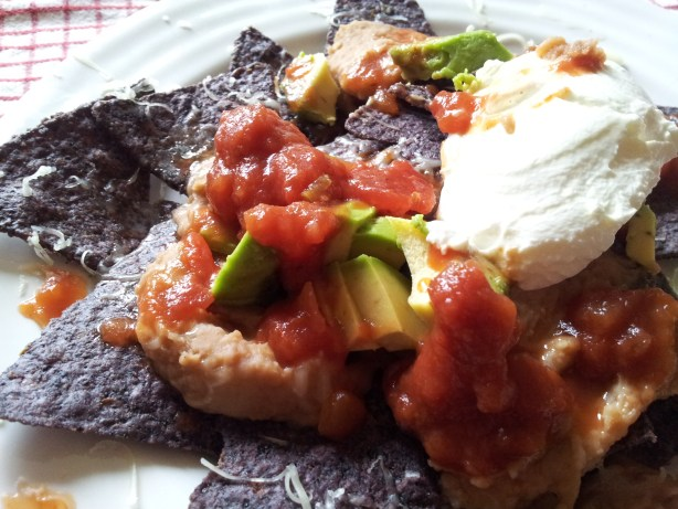 Plate of nacho (corn) chips with salsa, sour cream, avocado, and cheese