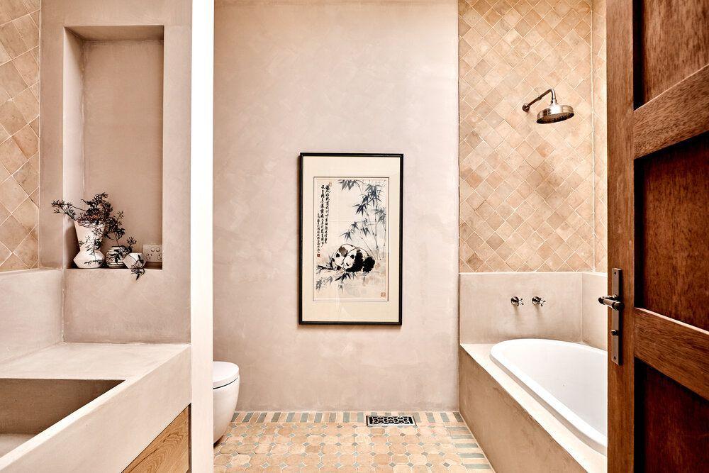 Zona de baño de tonos neutros claros, arcilla, revestido en cerámica artesanal y tadelakt, sostenible. (Studio Ezra)