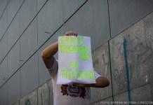 """Un hombre sosteniendo un cartel escrito a mano en el que se lee: """"somos trabajadores de televisión"""""""