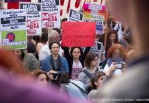 """Mujeres manifestándose en la marcha por el día internacional de la no violencia contra la mujer. En el centro de la foto sobresale una mujer con un cartel que dice """"No más violencia a las trabajadoras sexuales, más amor""""."""