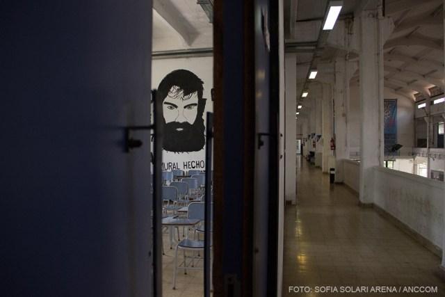 imagen de un pasillo y una puerta entornada que deja ver la imagen del rostro de Santiago Maldonado en la pared.