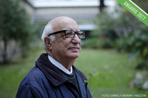 Domingo Bresci, con sus anteojos de marco grueso, posa de perfil y mira hacia arriba.