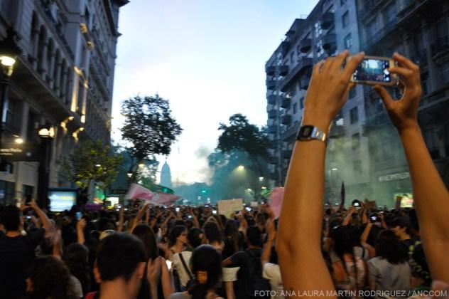 Una persona con un celular sacando una foto de la marcha. Muy lejos está el Congreso.