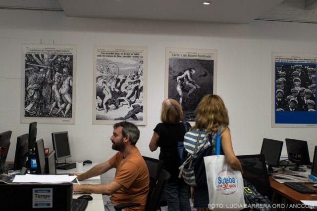 Un periodista del diario Tiempo Argentino trabajando mientras dos mujeres miran imágenes de la muestra en la pared