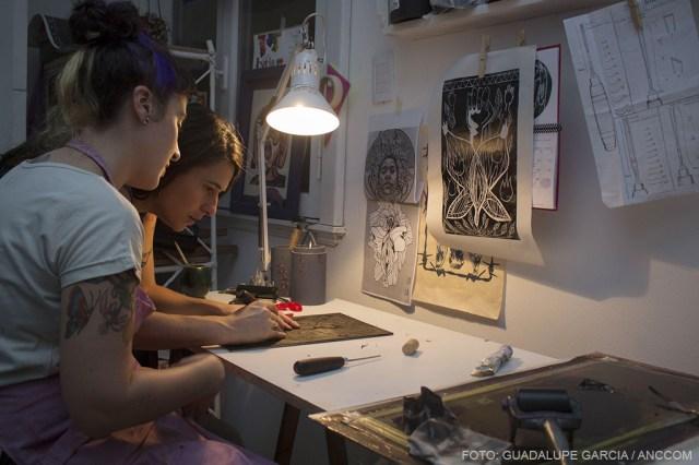 Dos mujeres tallando madera sobre un escritorio, se observan alrededor afiches colgados.