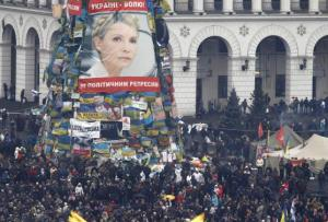 Anti-government protesters stand front of a poster showing jailed Ukrainian opposition leader Tymoshenko in the Independence Square in Kiev
