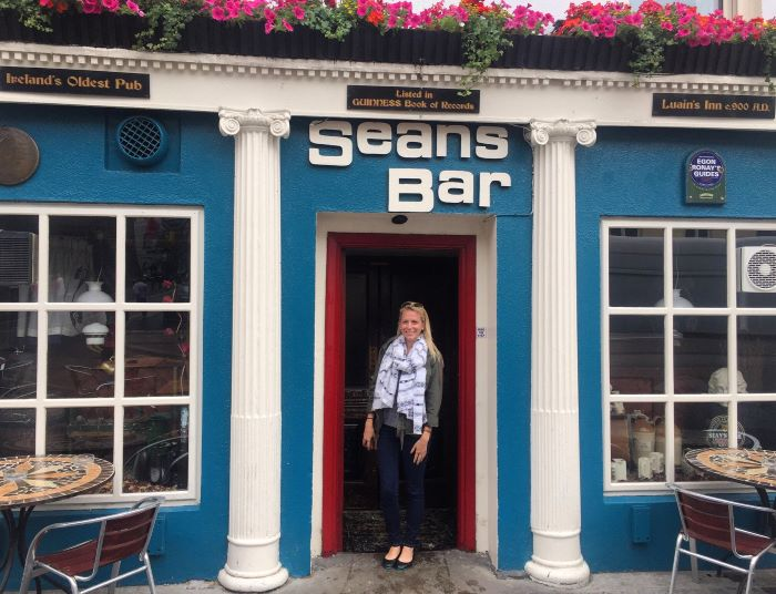 A woman standing in front of a bar - Sean's Bar - one of the things to do between Dublin and Galway.