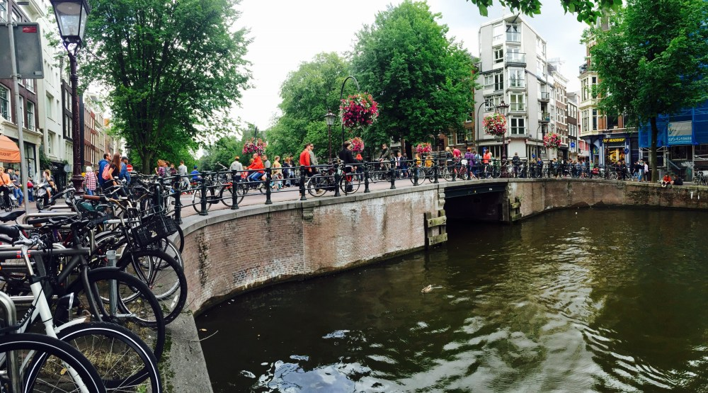 Bicycles lining a bridge and canal in Amsterdam.