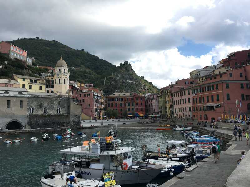A photo of the town of Vernazza. The photo is taken from the harbour and you can see the waterfront, boats and colorful buildings.