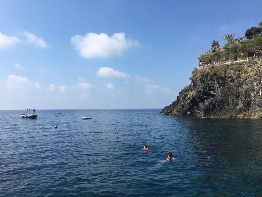 A photo of two people swimming in the water in Manarola. There is a small boat in the background.