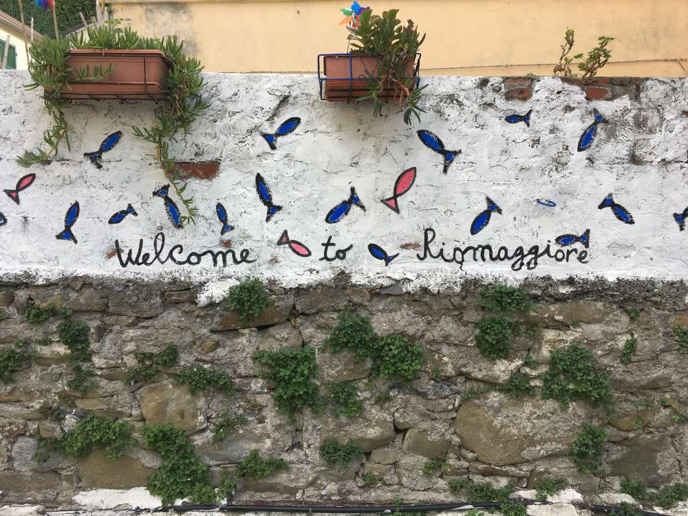 "A painted sign that says ""Welcome to Riomaggiore"""