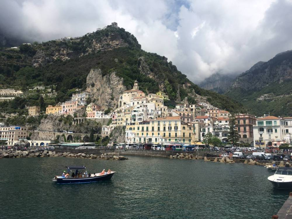 A photo of the town of Amalfi from the pier. There is a boat on the water.