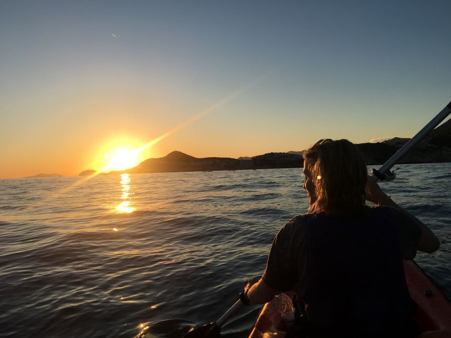 A photo of a woman on a kayak in Dubrovnik at sunset.