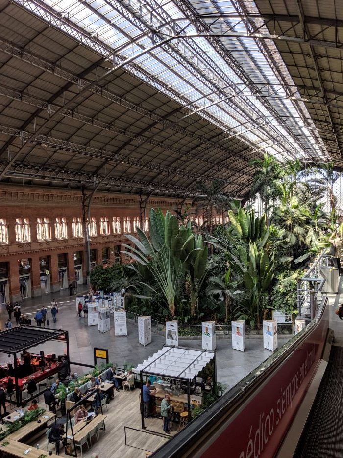 The photo of the train station in Madrid with plants and trees in the background.