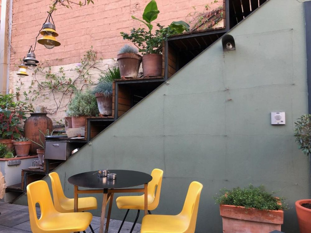 Four yellow chairs around a table with several potted plants at restaurant in Barcelona