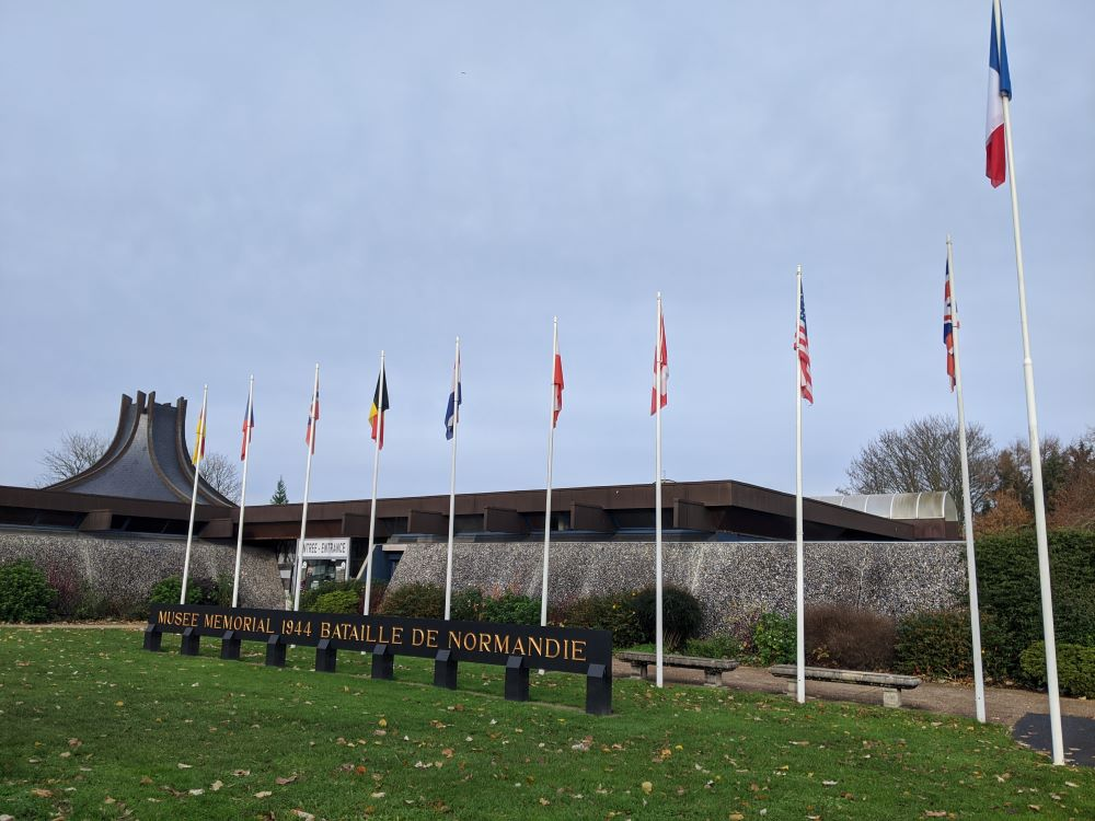 Several international country flags in front of the Battle of Normandy Museum in Bayeux.