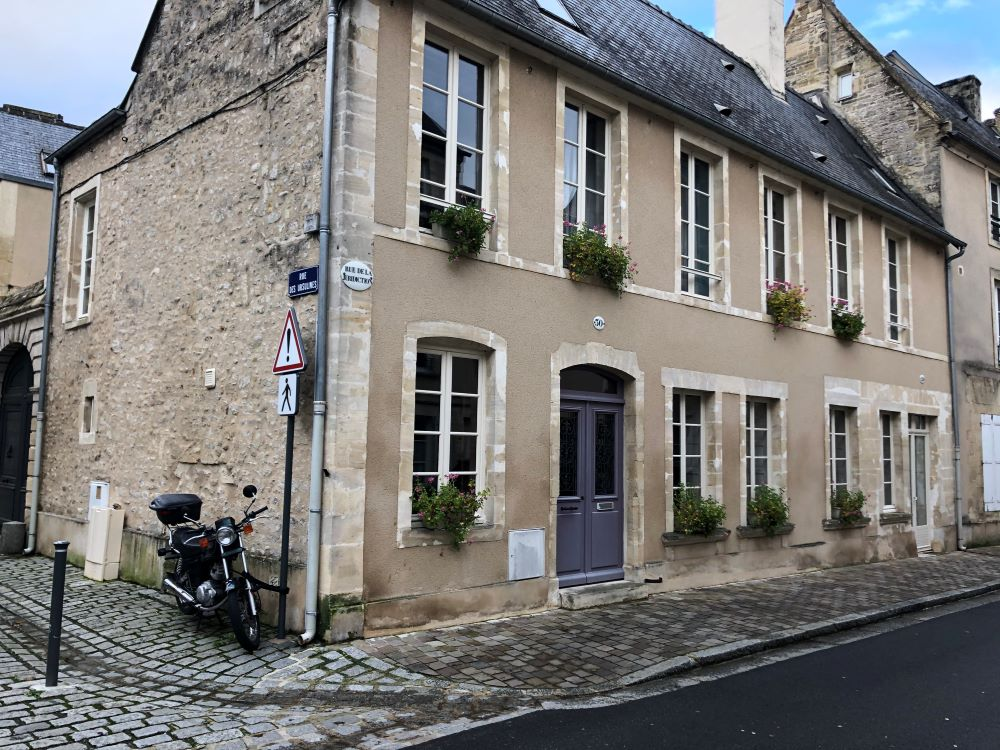 A sandstone house in Bayeux with a light purpose door.