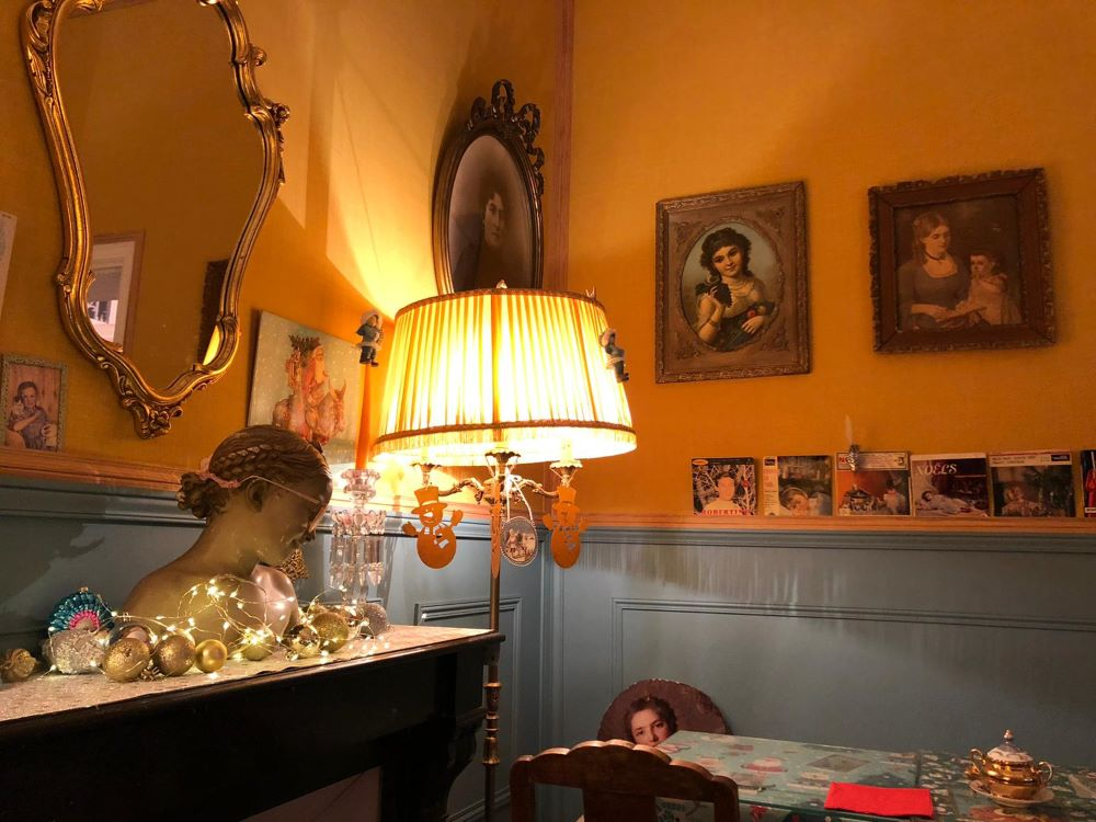 The interior of a cafe in Bayeux - yellow wallpaper, ancient photographs and dim lighting.